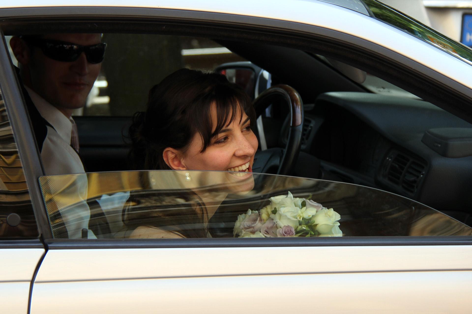 Esküvői kocsiból kitekintő menyasszony